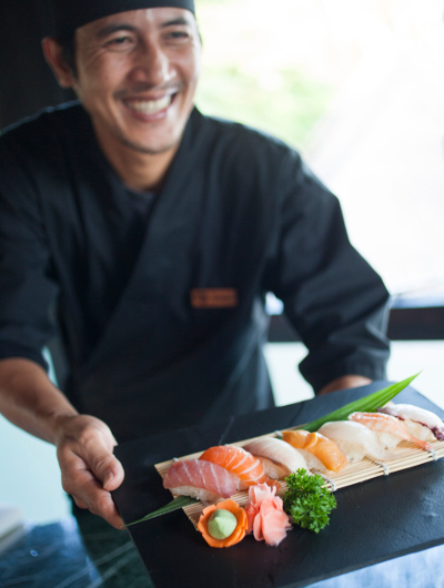A chef holds a dish of prepared sushi at Nala Rah at Outrigger Konotta Maldives Resort