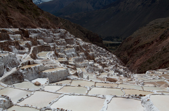 The salt mines of Maras cascade down a hillside in the Andes Mountains of Peru.