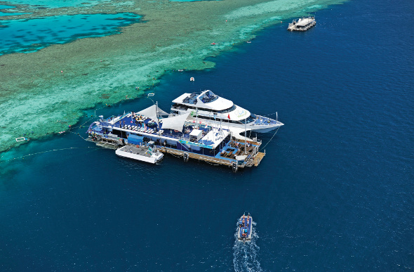 An aerial view of the Reefworld pontoon in the Whitsundays, sitting on the edge of Hardy Reef.