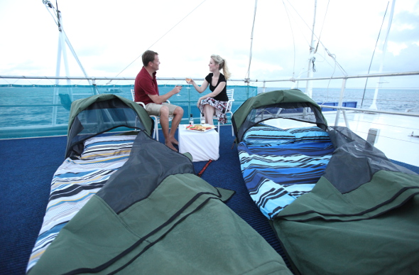 A couple share a toast on the top deck of Reefworld pontoon in the Whitsundays, with their swags in the foreground.