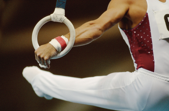 A close-up of a male gymnast on the rings.