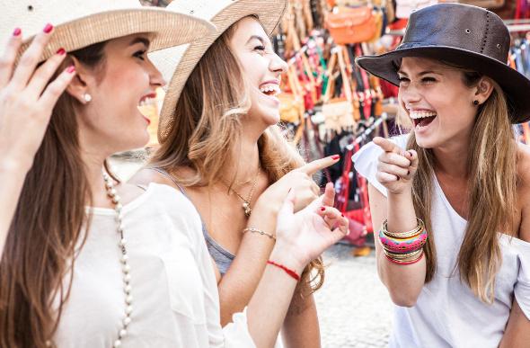 Women try on hats at a market in Rio de Janiero, Brazil.