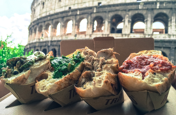 Three trapizzino lined up with the Colosseum in the background