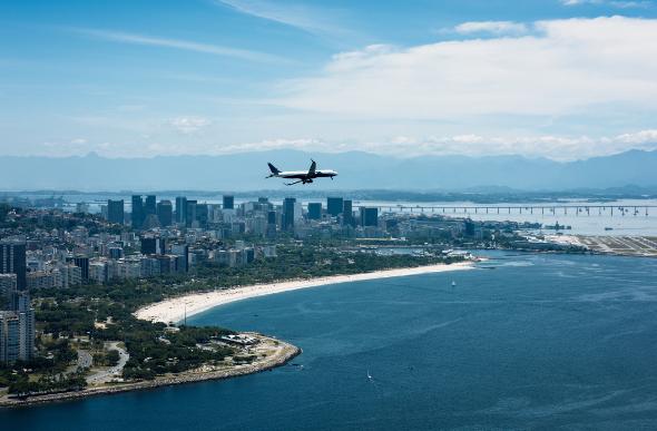 Plane flying over coastal city