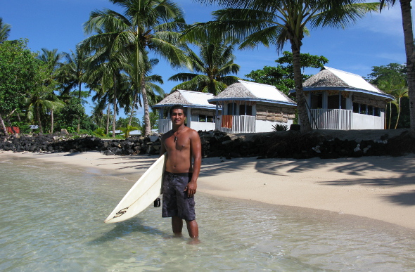 A Samoan surfer standing in ankle-deep water