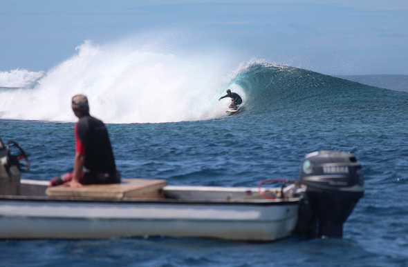 A surfer riding a wave in Samoa