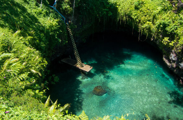 A deep hole with clear water and a ladder