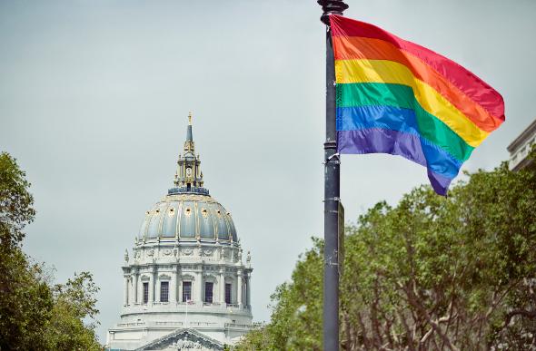 A gay pride flag flying near San Francisco building