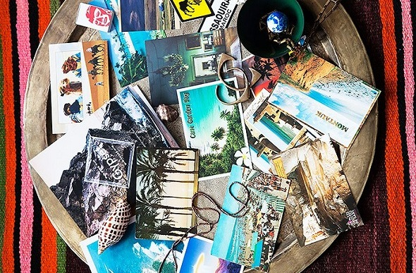 Flatlay image of a bowl of postcards and jewelry.