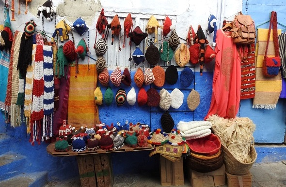 Colourful knitted beanies, scarfs and bags on display in a small market stall.