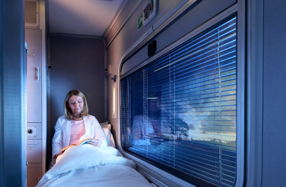 A woman relaxes with a book in her First Class sleeper carriage on board the Spirit of the Outback.