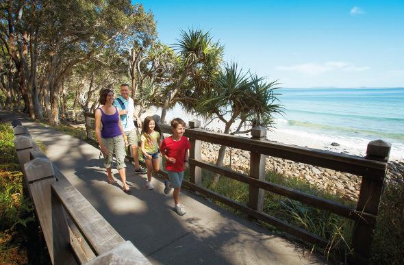 A family take a walk along the coastal path at Noosa.