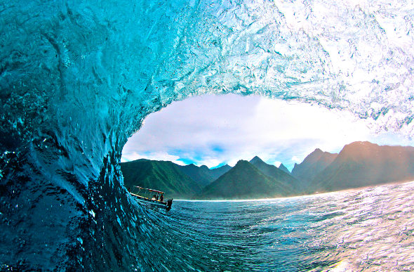 The mountainous shoreline can be seen through a curling wave at Teahupo'o in Tahiti.