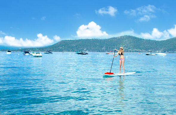 A woman goes stand-up paddleboarding on Lake Tahoe in the US.