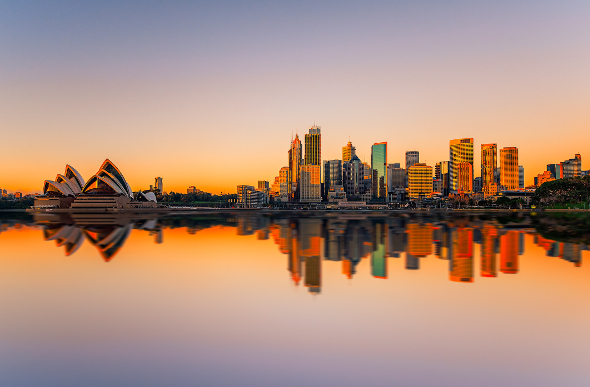 The Sydney Opera House and city skyline reflect in the harbour at sunset.