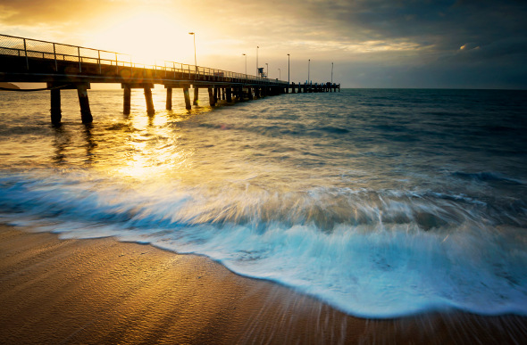 Sunset bathes a pier in Cairns in a golden glow as the foamy tide rolls in.
