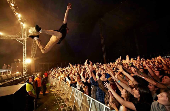 Performer diving off the stage into crowd of people