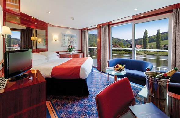 A luxurious river cruise suite with balcony and large bed