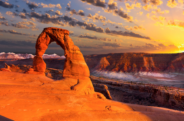The Delicate Arch rock formation glows orange as the sun sets in Utah's Arches National Park.