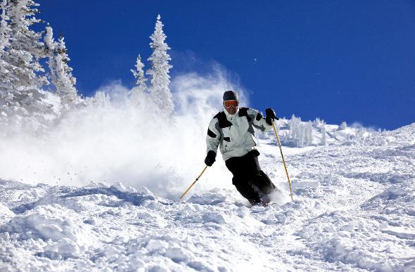 A skier kicks up powder on a blue-sky day at Snowbird ski resort in Utah.