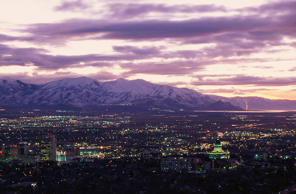 Salt Lake City twinkles at twilight, with snow-capped peaks in the background.