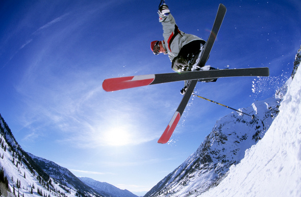 A skier gets airborne against the bright blue sky at Utah's Snowbird ski resort.
