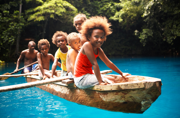 Kids sitting in a canoe over the blue water of Nanda Blue Hole