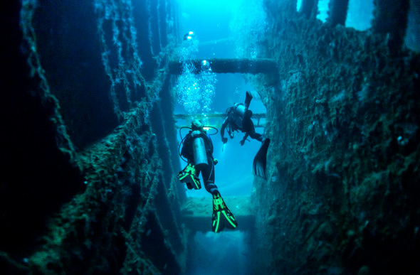 Two divers explore the wreck of the SS President Coolidge in Vanuatu.