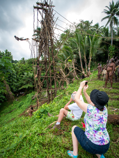 A Vanuatu local jumping from a wooden tower with vines around his ankles