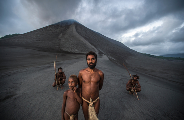 Four locals with spears standing in front of My Yasur on Tanna