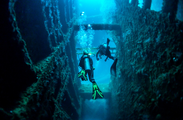 Two scuba divers exploring a ship wreck in Vanuatu