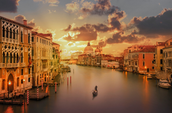 A lone gondolier cruising the Venice canals during sunset