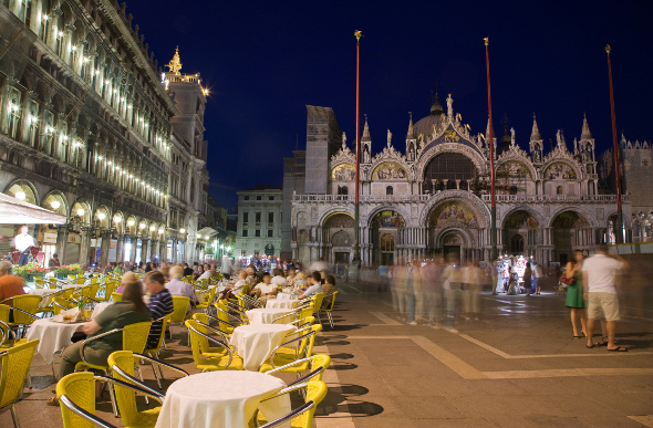 People eating and walking in St Mark's Square at night