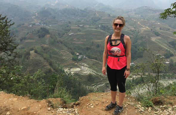 Flight Centre Travel Expert Cherie Horley stands on a mountainside in the northern Vietnamese region of Sapa, as terraced rice paddies unfold in the distance.