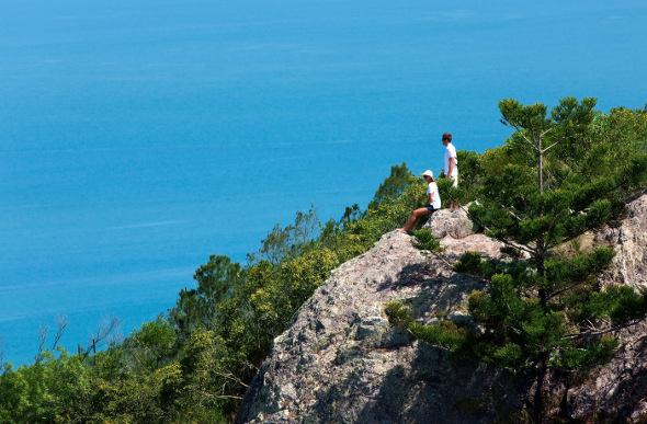 Bushwalkers rest at Passage Peak against a backdrop of blue ocean.