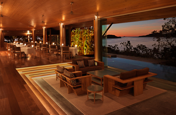 The Long Pavilion at qualia set up for dining as the sun sets over the Whitsundays.