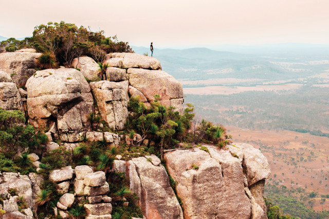 man standing on edge of cliff at dusk.