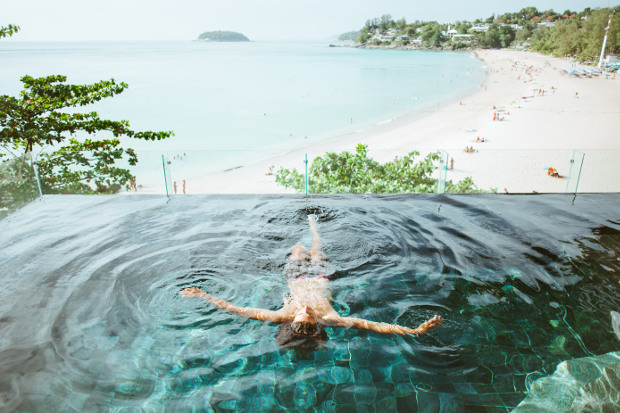 A woman relaxing in an infinity edge pool overlooking the beach and ocean