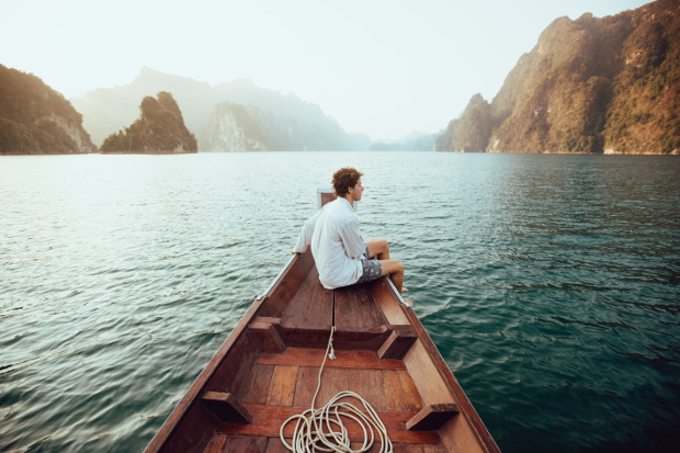 A man sitting at the stern of a canoe floating past some large rock formations in the ocean