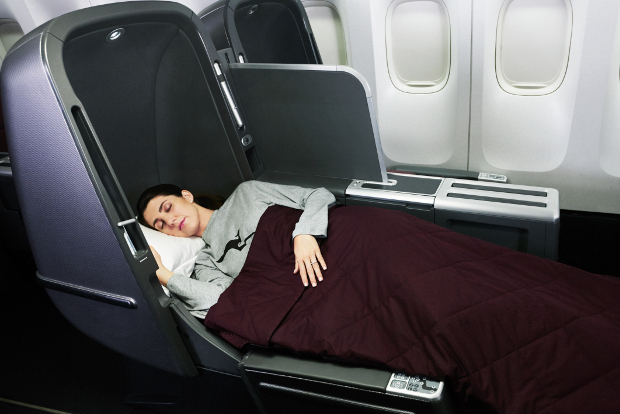 A Qantas passenger sleeping in a lay flat business class seat