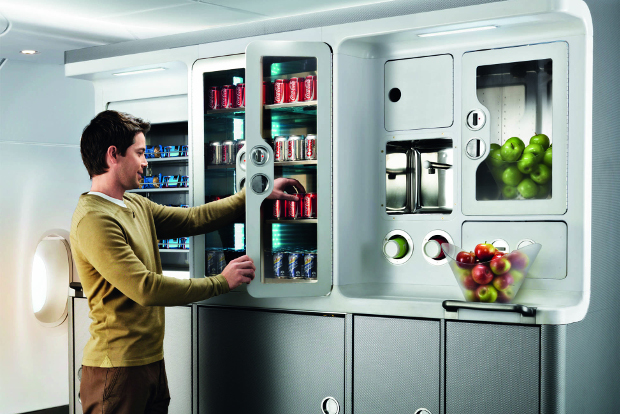 A man taking a Coke from the fridge of the A380 lounge