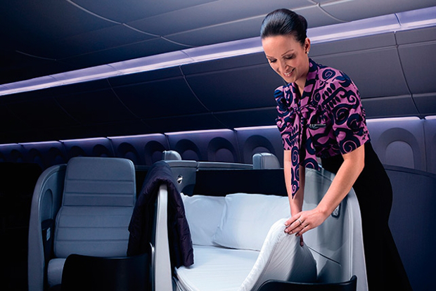 An Air New Zealand flight attendant setting up a lie-flat business class seat