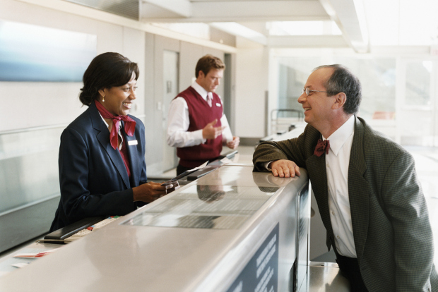 A man talking to a customer service agent at the airport
