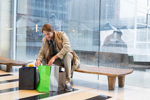A man sitting at the airport smiling and looking into a shopping bag