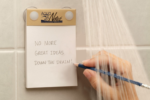 A person writing a note in the shower on the AquaNotes pad