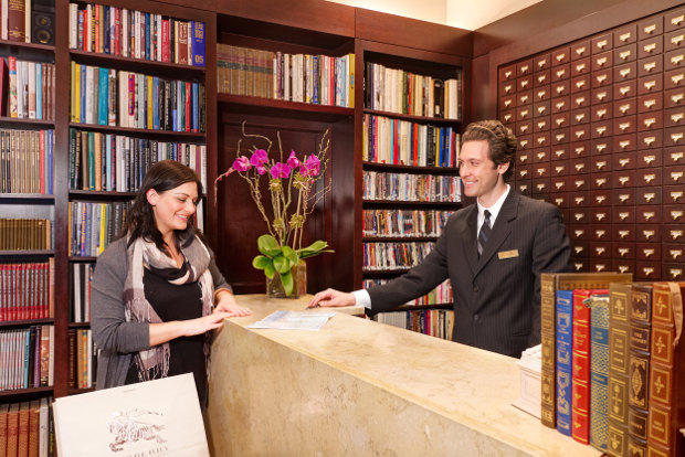 A man and woman surrounded by books at The Library Hotel's reception desk in New York.