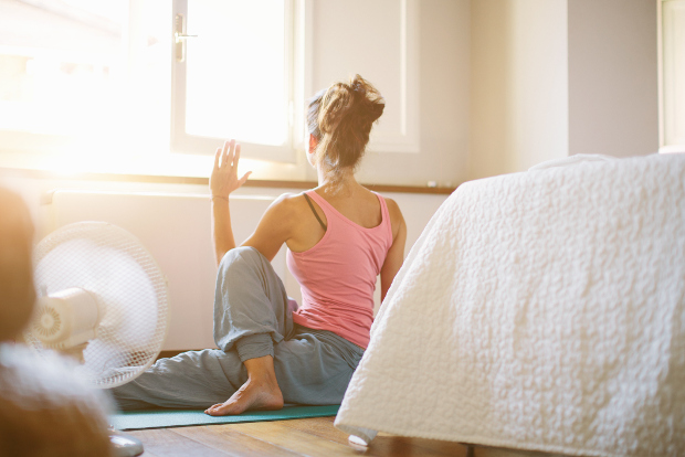 A woman does yoga in her hotel room.