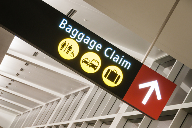 An airport sign pointing to the baggage claim area