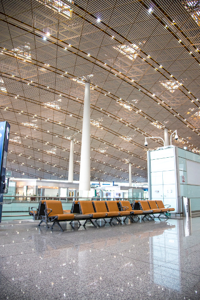Interior view of the Beijing airport featuring a yellow tinted mesh covered ceiling