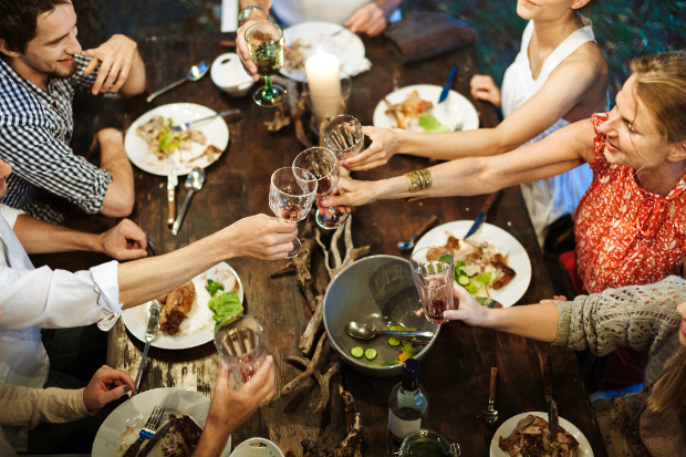 A group of friends clinking glasses over a meal